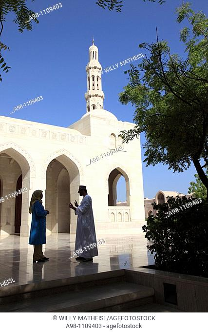 Omani man and woman talking outside in front of Grand Mosque Sultan Qaboos, Muscat, Sultanat of Oman, Asia