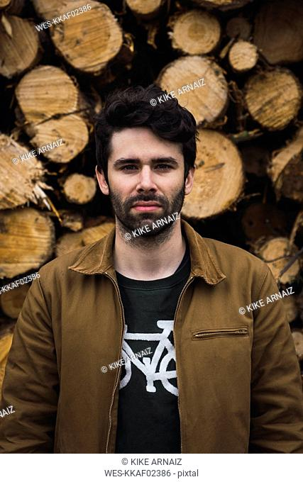 Portrait of young man in front of of stack of wood
