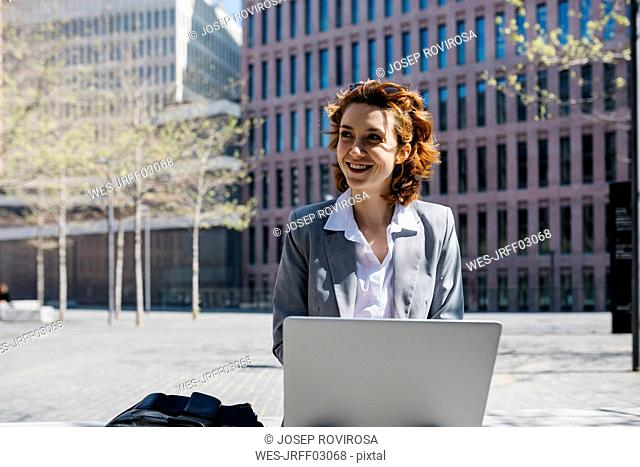 Young businesswoman with red shoes, sitting on a bench in the city, working on laptop