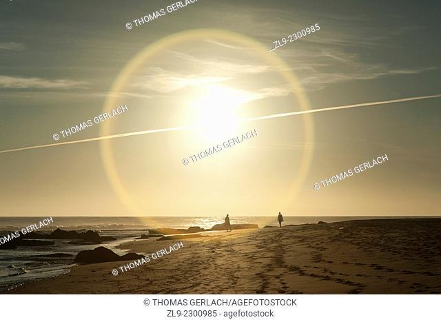 Sunset on sandy beach with halo around the sun and jet trail, Trafalgar beach, Cadiz, Spain