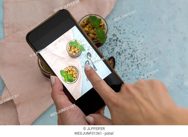 Woman's hand taking photo of dessert with smartphone, close-up