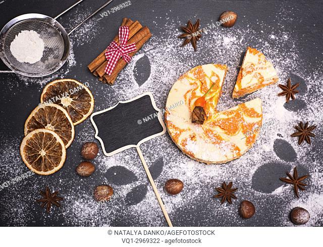 Cheesecake with pumpkin sprinkled with powdered sugar on a black background, top view