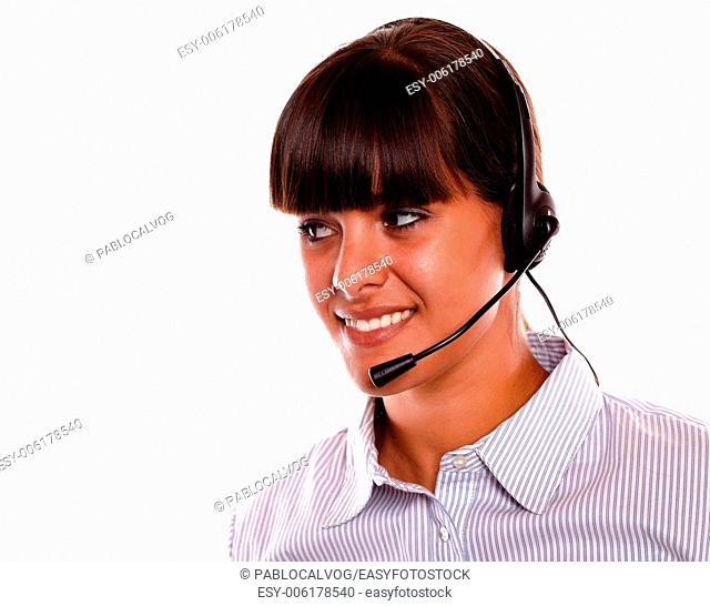 Portrait of a smiling young woman using earphone looking to her right on isolated background - copyspace