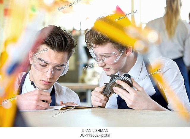 High school student measuring cog with calipers in shop class as classmate takes notes
