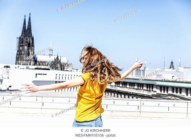 Germany, Cologne, woman dancing on roof terrrace