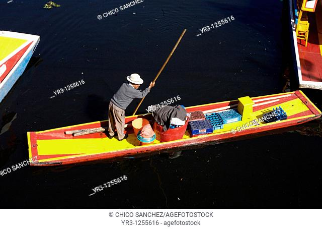 An elderly man who sells food to tourists uses a pole to navigate his boat through a canal in Xochimilco on the south side of Mexico City