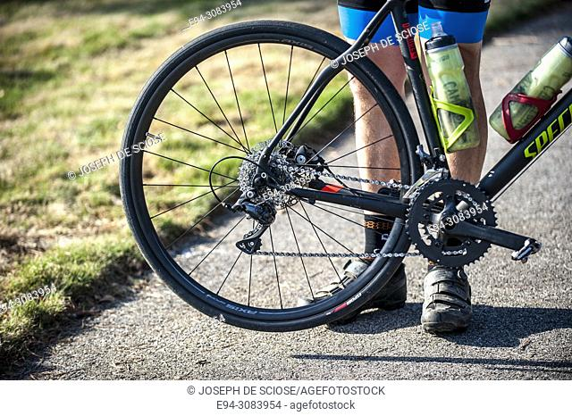 A partial view of a bike rider's legs next to a bicycle wheel