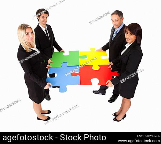 Group of business people assembling puzzle