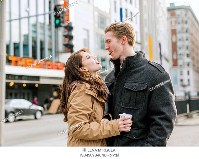 Young couple standing in street, face to face, sticking out tongues