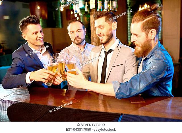 Celebrating completion of hard working day: group of cheerful colleagues clinking beer glasses together while standing at bar counter
