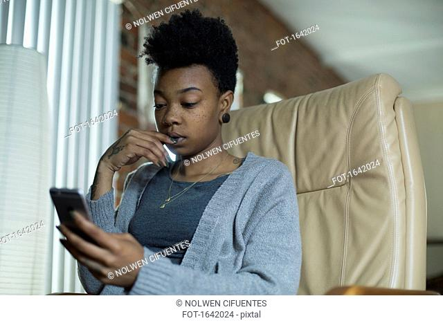 Low angle view of woman using mobile phone while sitting on armchair at home