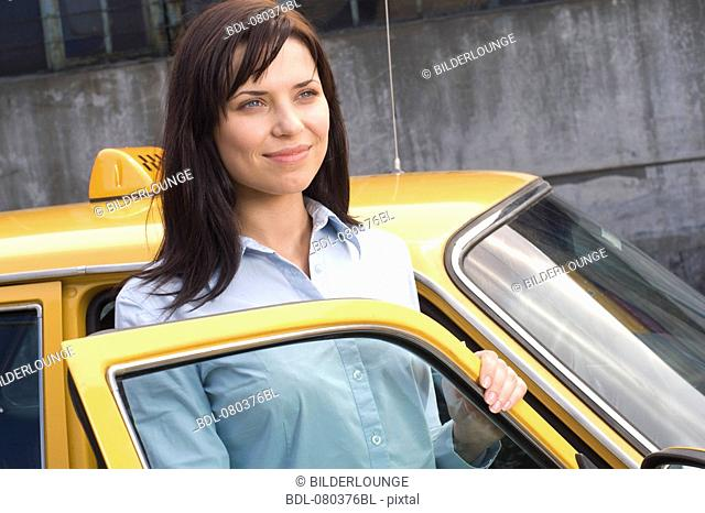 portrait of young business standing at open door of yellow taxi