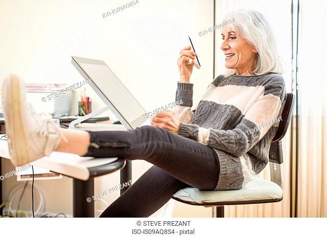 Portrait of senior woman sitting at computer holding smartphone with foot on desk