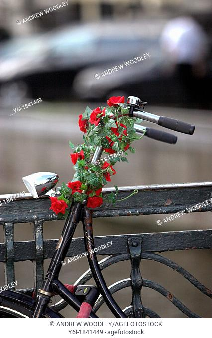 Red plastic roses decorate the stem and handle bars of bicycle Amsterdam The Netherlands
