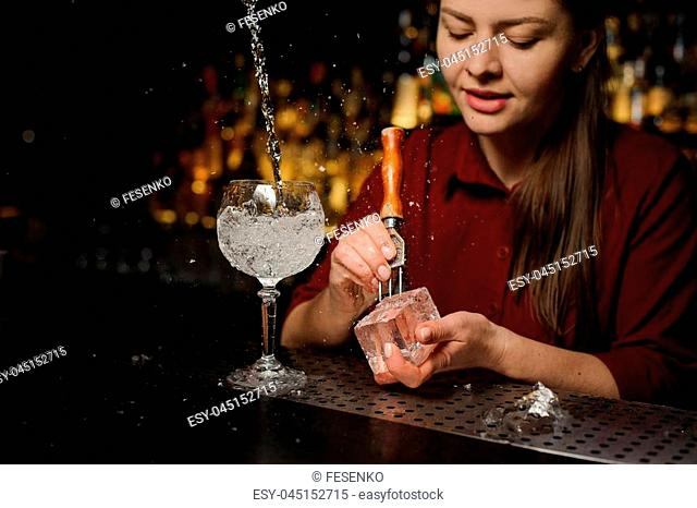 Beautiful woman barman preparing an ice cube for making a fresh and tasty Aperol syringe cocktail
