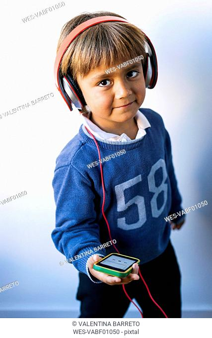 Little boy listening to music of his smartphone with headphones