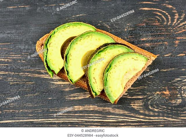 Sandwich with slices of fresh avocado on wooden background, top view