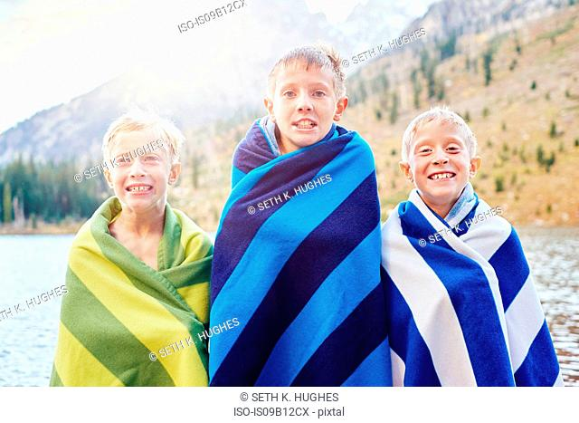 Portrait of male twins and brother wrapped in blankets, shivering, Grand Teton National Park, Wyoming, USA