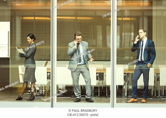 Business people on cell phones and taking notes at conference room window