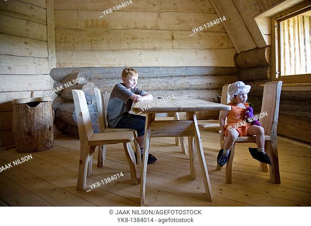 Serious Emorional Kids, Boy and Girl Sitting at Wooden Table in Old Blockhouse
