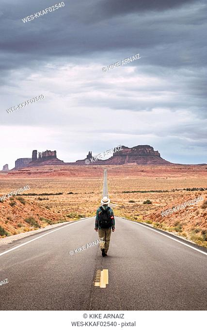 USA, Utah, Man with backpack walking on road to Monument Valley