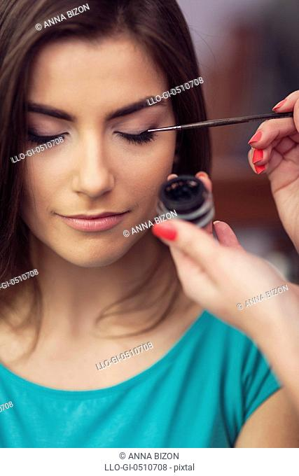 Applying eyeliner from inkwell by makeup brush. Debica, Poland