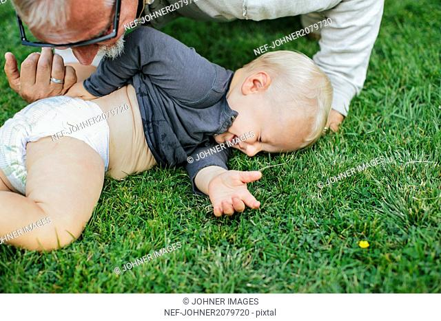 Grandfather playing with grandson on lawn