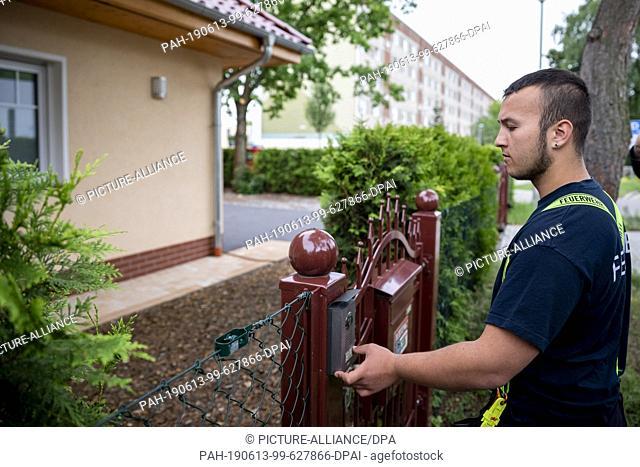 13 June 2019, Brandenburg, Oranienburg: Pascal Lehmann, firefighter at the Germendorf Volunteer Fire Brigade, rings the bell at a house in Oranienburg during...