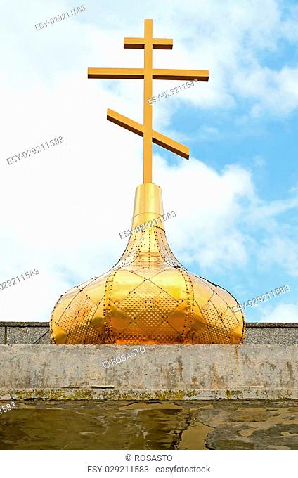 The dome of the Orthodox cross on a blue sky background