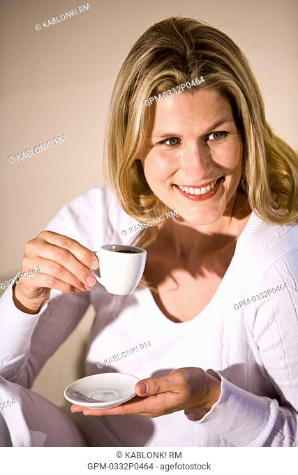 Portrait of mid adult woman holding coffee cup in modern downtown loft apartment