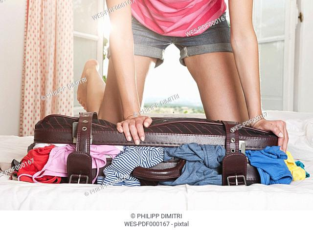 Italy, Tuscany, Young woman pushing stuffed suitcase in hotel room
