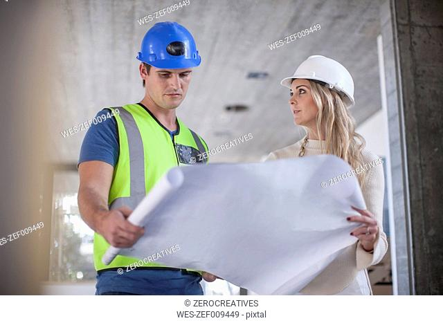 Construction worker and woman looking on construction plan