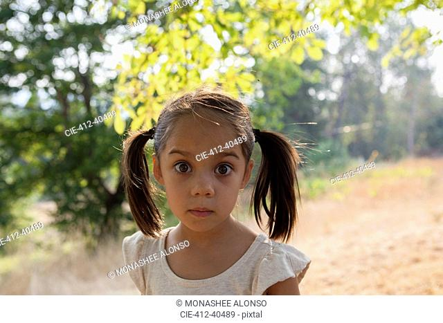 Portrait wide-eyed girl with pigtails in yard