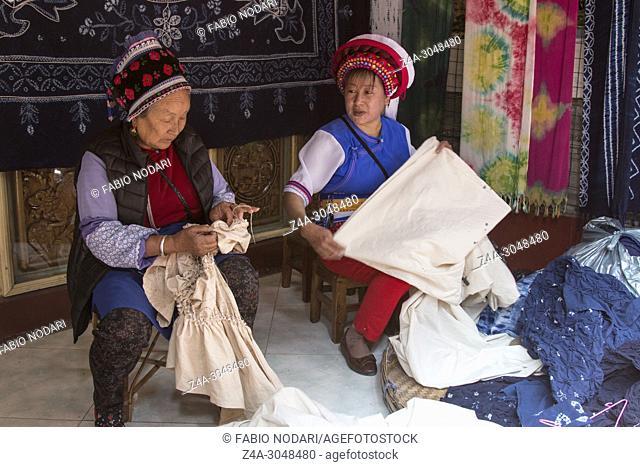 Bai women hand dyeing fabrics with indico blue