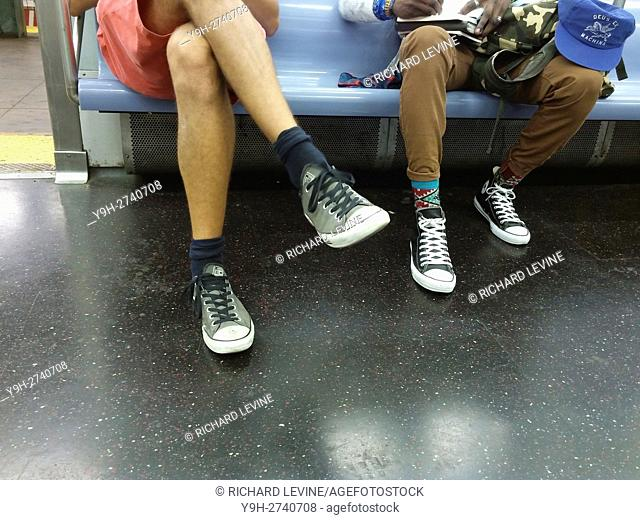 Hipster subway riders traveling through Bushwick, Brooklyn in New York wearing their Converse All-Stars sneakers