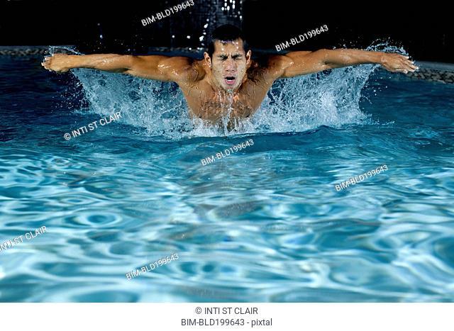 Pacific Islander man swimming in swimming pool