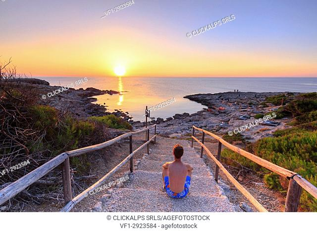 Tourist watches the sunset at Cala Tramontana, Tremiti Islands, Foggia, Puglia, Italy