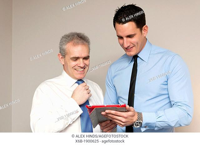 Business colleagues, one young and one older, discuss work using tablet computer