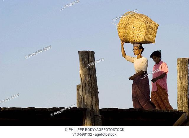 Woman carrying a big basket on her head on the U Bein bridge in teak wood in the old royal city of Amarapura near Mandalay, Myanmar