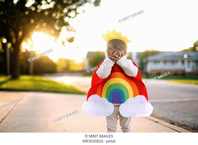 Young girl standing on a pavement, wearing colourful costume with rainbow, sun and clouds, covering face with her hands