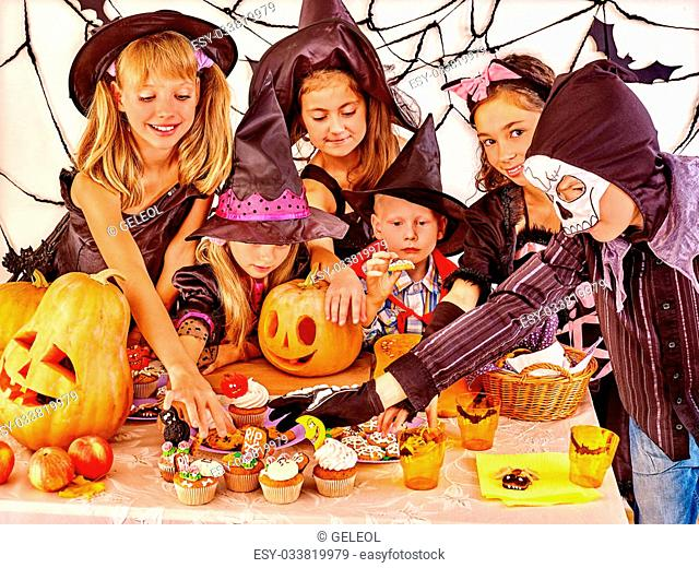 Halloween party with children holding carving pumpkin