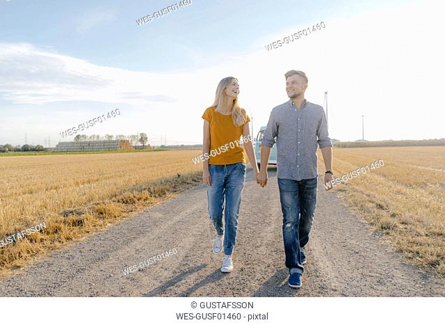 Young couple walking on dirt track at camper van in rural landscape