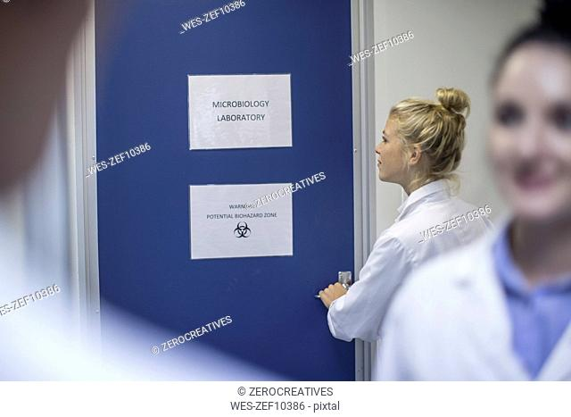 Woman in lab coat opening door to microbiology laboratory
