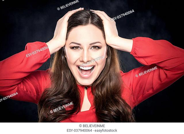 Surprised smiling brunette woman over dark background
