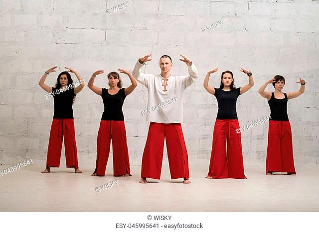 Group of women and their male trainer doing yoga shot against brick wall