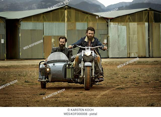 Two men with full beards in motorcycle with sidecar