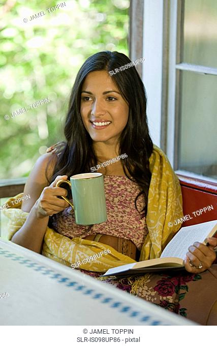 63cdb740 Woman reading a book in veranda Stock Photos and Images | age fotostock