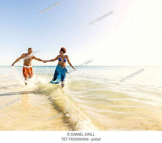 Mature couple running in sea
