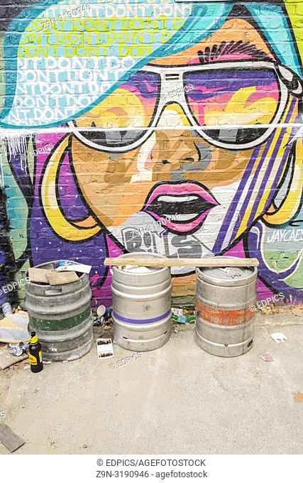 graffito mural showing a woman with sunglasses, in the foreground aluminum beer barrels, london, england