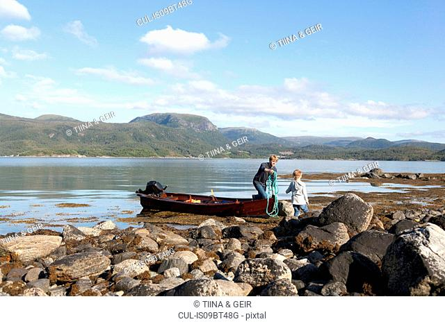 Mature man passing rope to son from rowing boat, Aure, More og Romsdal, Norway